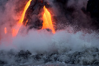 Lava, breaking surf and steam